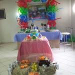 Mesa de bolo e mesa de doces ao fundo